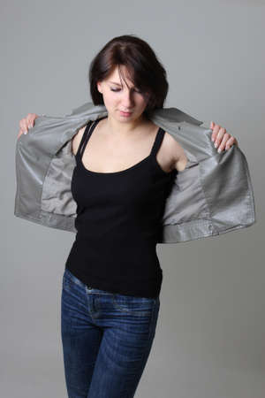 woman in jeans and leather jacket over grey background Stock Photo