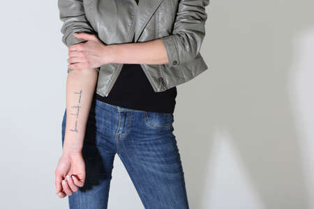 woman showing tattoo on her hand over grey photo