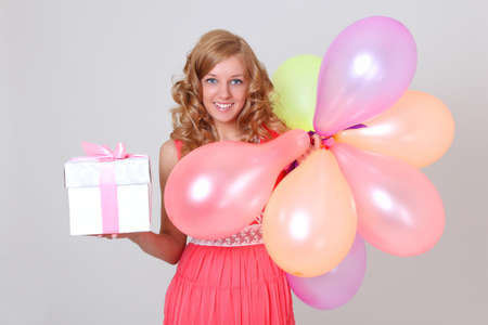 Happy blonde woman with colourful balloons and gift in dress photo