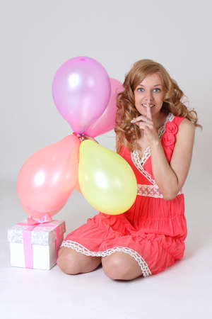 Blonde birthday girl with gift and balloons showing shh sign photo