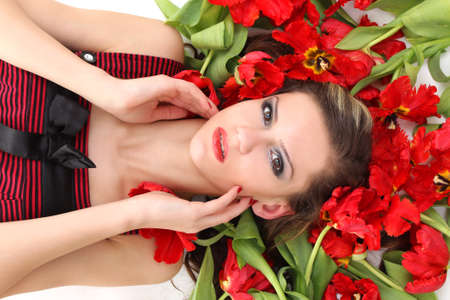 beautiful girl lying on the red flowers photo