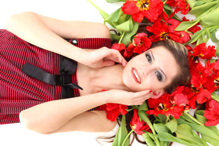 young beautiful girl lying on the red tulips photo