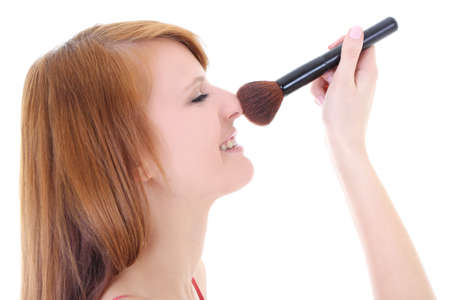 Happy teenager with make-up brush over white photo