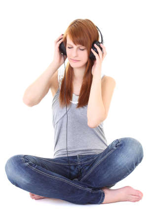 Happy teenager with headphones sitting over white Stock Photo - 13425239