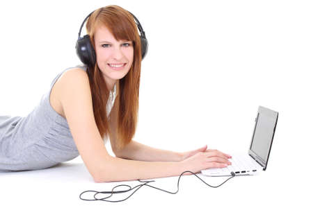 Happy teenager with headphones and laptop lying photo