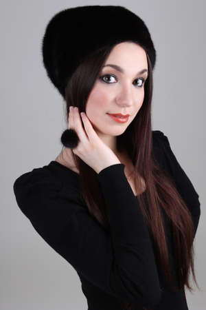 Happy woman in black fur hat and ring photo
