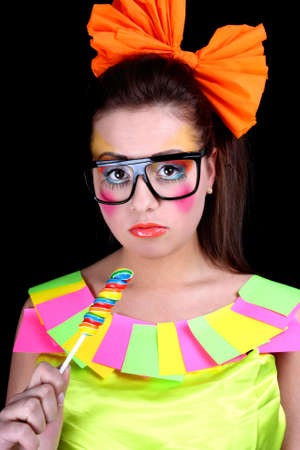 Woman in doll style with creative make-up and lollipop over black photo