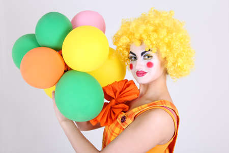 Funny clown in costume with colourful balloons photo