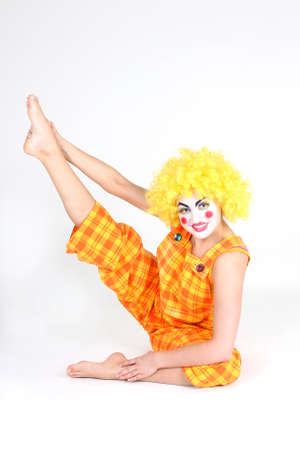 Clown in colourful costume with bow doing gymnastic photo