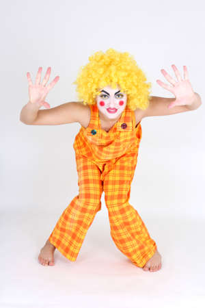 Clown in colourful costume with make-up showing hands photo