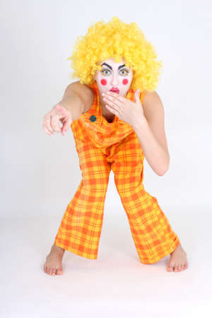 Clown in colourful costume showing something and surprised photo