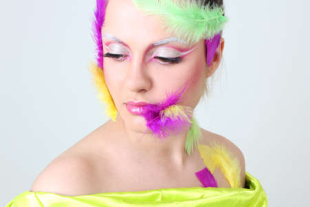 Woman with creative make-up and feathers like a bird photo
