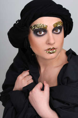 Woman with black make-up and scarf on head photo
