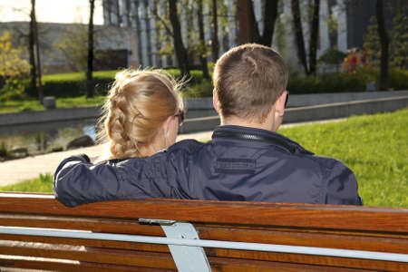 Young couple sitting on the bench in park photo