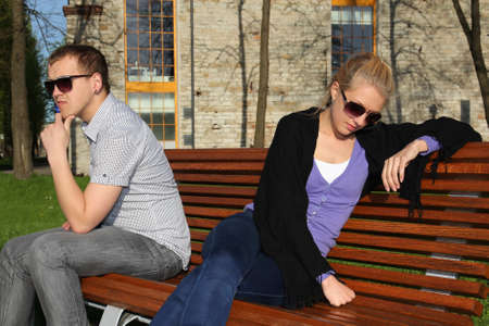 Sad couple sitting in park on the bench photo