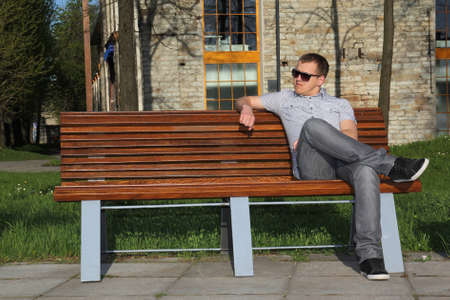 Man in sunglasses sitting in park on the bench photo