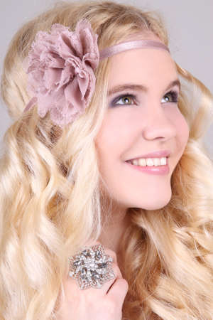 Happy closeup portrait of blonde girl with bow and ring photo