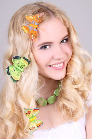 Happy girl with butterfly in hair and nacklace photo