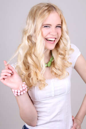 Funny blonde girl in studio over grey background photo