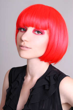 Portrait of woman in red wig over grey