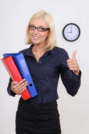 young succesful businesswoman with folders thumbs up photo