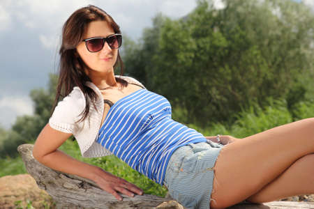 young sexy model sitting on a log in park photo