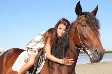 girl riding a horse on the background of the sea photo