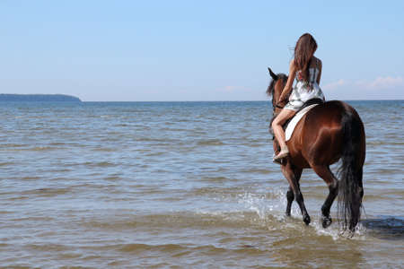 Woman with big brown horse bathing in sea photo