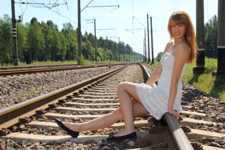 young woman sitting on the railway photo