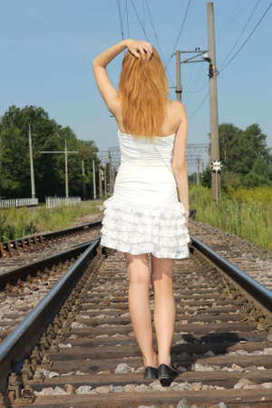 young woman in white dress on the railway photo
