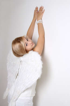 highkey: Young blonde woman with white wings