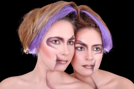 coloration: portrait of beautiful twins isolated over black Stock Photo