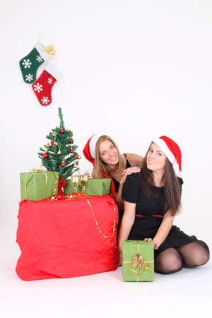 Happy girls in christmas time with santa hats photo
