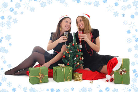 Two girls sitting and drinking champagne in christmas time with snowlakes background photo