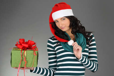 attractive girl in santa hat and striped dress with gift photo