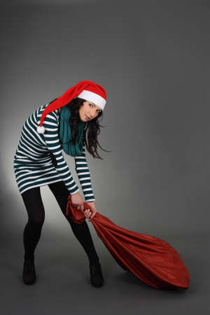 attractive woman in santa hat with bag over grey photo
