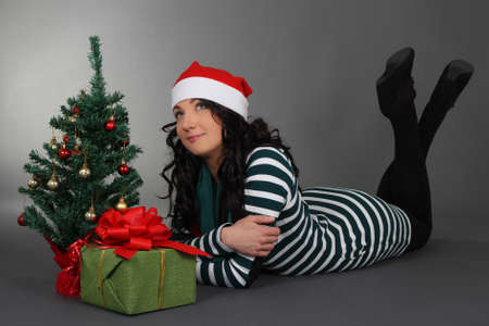 lying woman in santa hat with gift and tree over grey photo