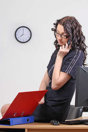 sexy businesswoman in the office on the phone photo