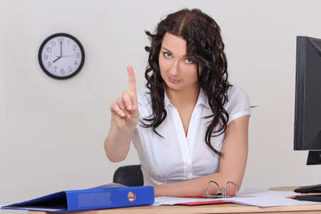 business woman pointing up with idea at desk in office photo