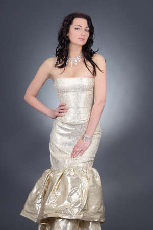 beautiful girl in golden dress posing over grey background photo