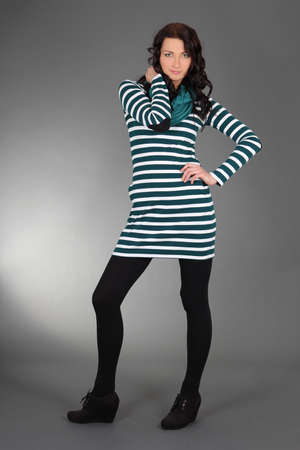 young attractive woman in striped dress posing over grey photo