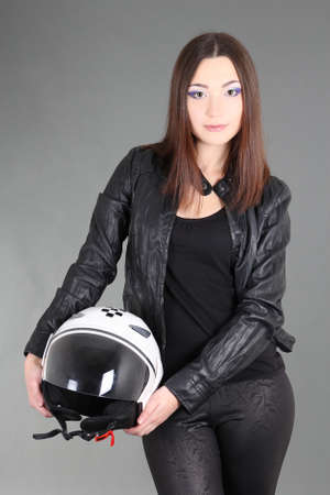 Beautiful woman with helmet in hands over grey photo