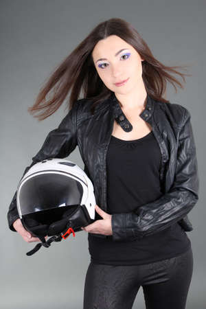 Young woman with helmet in hands over grey photo