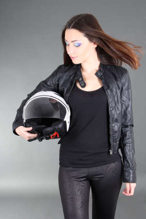 Young pretty woman with helmet in hands over grey photo