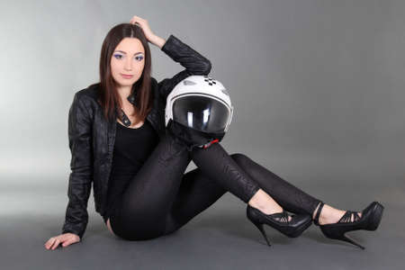 Young pretty woman with helmet sitting over grey photo
