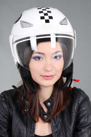 Woman in helmet on head over grey photo