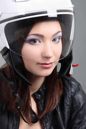 Beautiful woman in helmet on head over grey photo