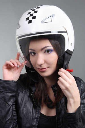 Biker in helmet on head over grey photo