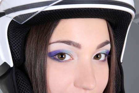 Woman's eyes with helmet on head over grey photo