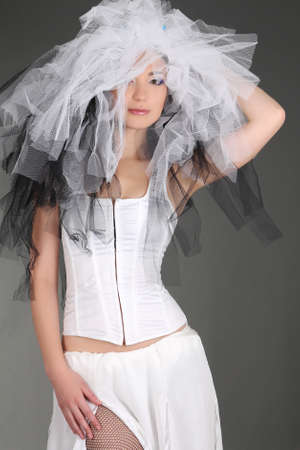 Woman in white dress with material on head posing over grey photo